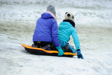 Two girls of teenagers together move down from a hill on the sledge. They warmly are also conveniently dressed. View from a back.