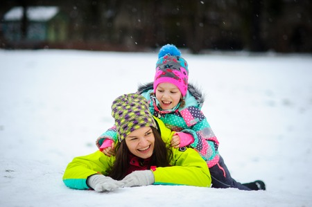 somersault: Lovely young woman and girl in bright jackets lie on snow. It is snowing. Mother and the daughter cheerfully flounder in snow. Snow is loved by both adults and children.