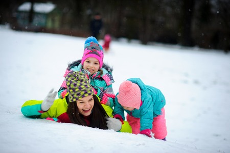 Young mother and two of her little daughters have put up a cheerful fight on snow. Woman lies on snow, and girls get to her on a back. Winter entertainments delight also adults and children.
