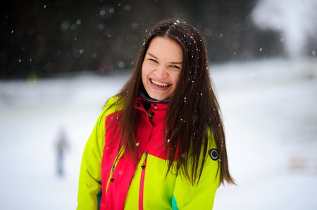 joyfully: Lovely young woman brunette in a bright jacket on walk in winter day. It is snowing. The woman stands without headdress and joyfully laughs. Snowflakes lie on dark hair. Stock Photo