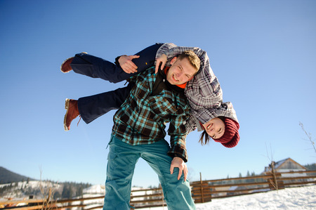rollick: Young man holding in his arms his girlfriend. Man sturdily built easily picks up a fragile girl. Young people having fun. Against the background of the blue sky.