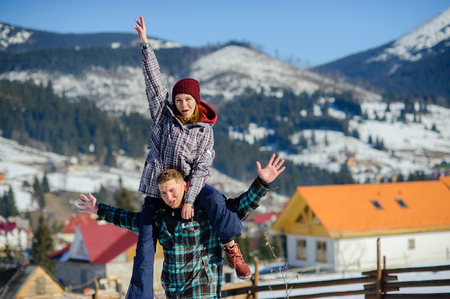 rollick: Young man holding his girlfriend on his shoulders. Against the backdrop of beautiful mountain scenery.