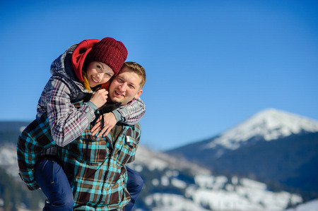 Young man holding his girlfriend on his shoulders. Girl embraces guy for neck. Against the backdrop of beautiful mountain scenery.