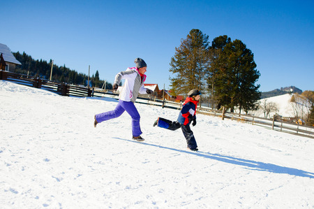 Woman and the boy of school age compete in run. Rural areas. Picturesque mountain landscape. Ground is covered with snow. Good mood. Healthy lifestyle. Stock Photo