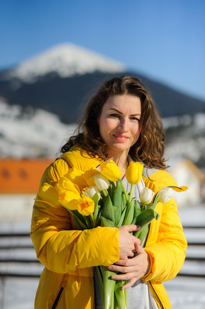 Charming woman with a bouquet of tulips against the background of snow-covered mountain tops. She is dressed in a bright yellow down-padded coat. Woman has a happy look.