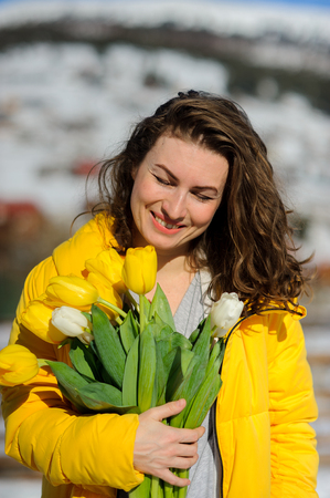 Charming woman with a bouquet of tulips against the background of snow-covered mountain tops. She is dressed in a bright yellow down-padded coat. Woman has curly hair and a charming smile. Stok Fotoğraf