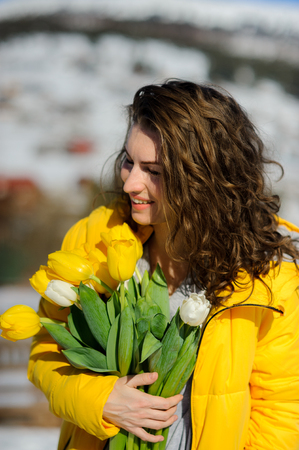 Charming young woman with a bouquet of yellow and white tulips. Curly hair, nice smile. Bright yellow coat blends with the flowers. Spring mood.