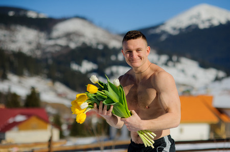 flaunt: Young man with a bouquet of flowers against the background of snow-covered mountains.