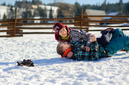 Young couple cheerfully flounders in snow