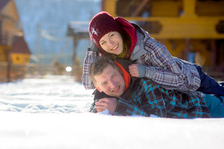 rollick: Young couple lies on snow. Girl has got on guys back. Serene winter day. Young people with pleasure flounder in snow. Stock Photo