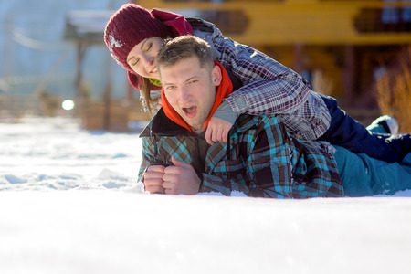 Young couple lies on snow. Girl has got on guys back. Serene winter day. Young people with pleasure flounder in snow. Stock Photo