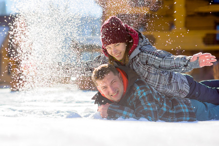 rollick: Young couple lies on the snow. The girl climbed onto the back of her boyfriend and sprinkled it with snow. Between them comic fight. Sunny winter day. Good mood. Young people smile