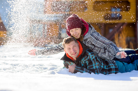 climbed: Young couple lies on the snow. The girl climbed onto the back of her boyfriend and sprinkled it with snow. Between them comic fight. Sunny winter day. Good mood. Young people smile