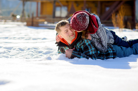 rollick: Young couple lies on the snow. Girl climbed onto the back of her boyfriend. She kisses the guy on the cheek. Sunny winter day.
