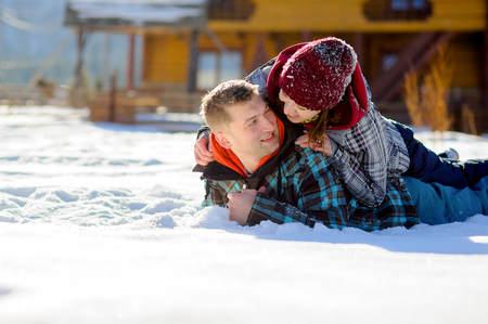 Young couple lies on the snow. Girl climbed onto the back of her boyfriend. Young people look at each other with love and tenderness. Sunny winter day. Good mood. Stock Photo