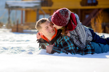 rollick: Young couple lies on the snow. Girl climbed onto the back of her boyfriend. Young people look at each other with love and tenderness. Sunny winter day. Good mood. Stock Photo