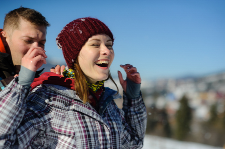 Young man carefully shakes snow from clothes of girlfriend. Girl happily smiles. Serene winter day. Blue sky. Stock Photo