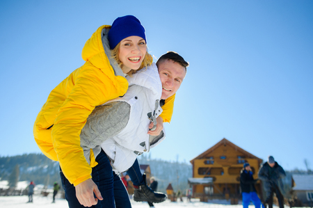 prank: Young man holding his girlfriend on his shoulders. Girl embraces guy for neck. Young people look in the camera and cheerfully smile. Against the background of mountains and blue sky.