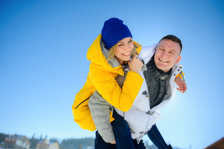 Young man holding his girlfriend on his shoulders. Girl embraces guy for neck. Young people look in the camera and cheerfully laugh. Against the background of the blue sky. Stock Photo