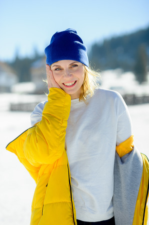 Portrait of the charming young woman. Sunny day, blue sky. The woman removes the bright yellow down-padded coat. To her hot and cheerfully.