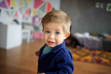 Portrait of little boy. Cute chid looks in camera serious look. Round big grey eyes, long eyelashes, chubby cheeks, vivid lips. Kid is funny and touching. Stock Photo