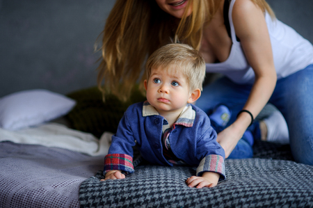 Amusing little boy lies on a big bed. Near him his young mother. She tenderly and carefully concerns the kid. Boy has a cute serious face, beautiful big eyes.