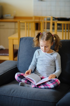 keen: The nice girl of younger school age reads the book. She sits having crossed legs on a soft sofa. The girl is keen on reading.