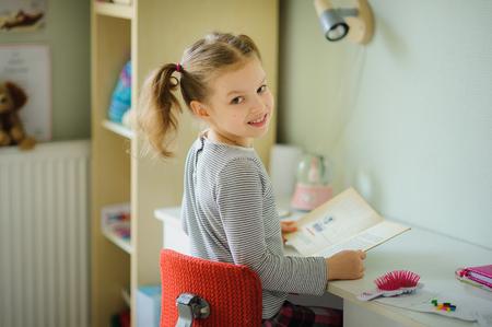 Malá školačka provádí domácí úkoly. Dívka sedí u stolu, který se napůl otočil k fotoaparátu a usmívá se. V ruce u ní otevřenou učebnici. Na stolní školní potřeby a různé osobní předměty.