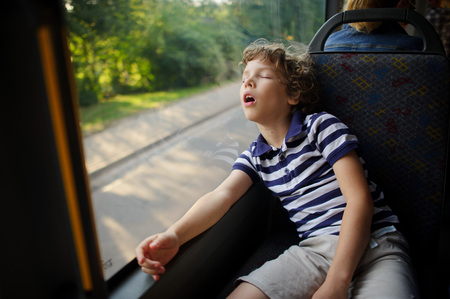 The little boy has fallen asleep in the bus. The tired child sleeps, having leaned against a window.