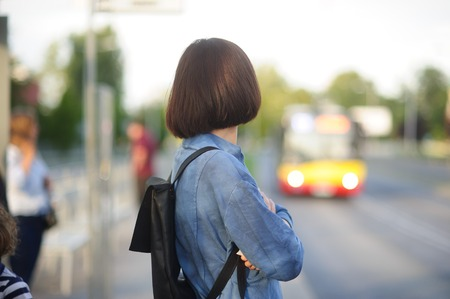 The young woman the brunette stands on the bus stop. She expects the bus. The woman is dressed in sports style. She high and slim. Behind shoulders at her a backpack. Stock Photo