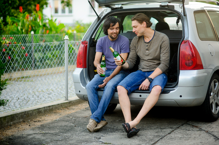 derive: Two young men drink beer from bottles. They have conveniently settled down in an open luggage carrier of the car. Friends derive pleasure from beer and communication.