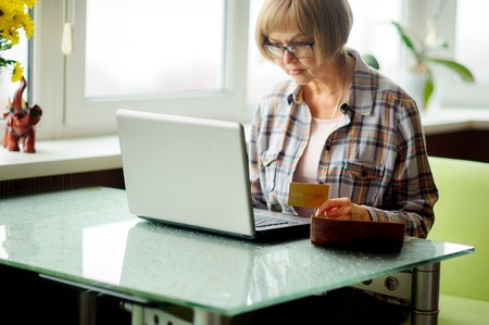 uses: The elderly woman looks in the laptop screen. She uses the computer for payment of accounts.