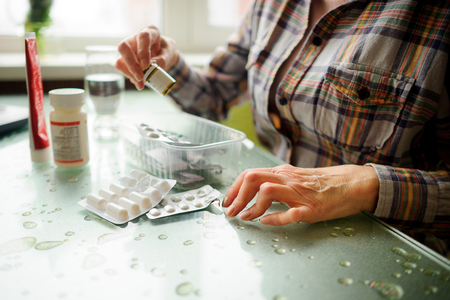 The woman having rheumatoid arthritis takes medicine. Hands are deformed.