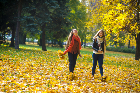 Mellow autumn. Two girls are students cheerfully spend time in the city park. Good weather, blue sky. Girlfriends throw armfuls of dry yellow leaves up and rejoice as children. Stock Photo