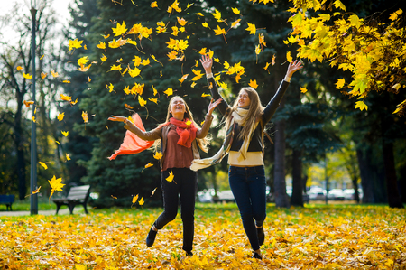 Two girls cheerfully spend time in the autumn park. The lawn in the park is completely covered with yellow leaves. Girlfriends throw dry yellow leaves up and dance in the rain from leaves.