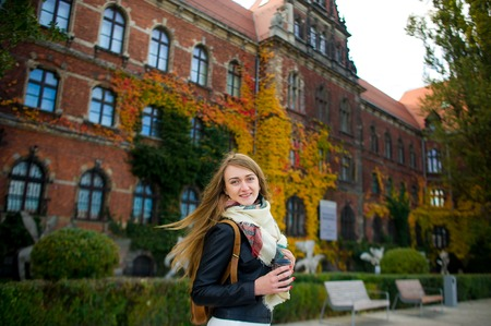 unusually: Mellow autumn. The lovely girl student has coffee. She stands near the building which is completely twined wild grapes. Motley leaves give to the building unusually beautiful look. Stock Photo