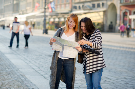 Two young women walk on unfamiliar city. Girlfriends go sightseeing. In hands women have a card. They are surrounded with fine architecture. Tourists have a good mood. Stock Photo