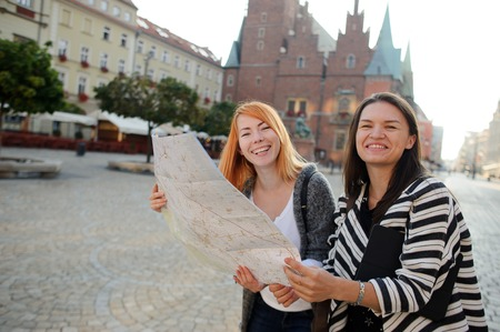 Two cute young women standing on the square of the beautiful European city. Tourists carefully consider the map of the area. Behind them are picturesque architecture. Girls have an excellent mood.