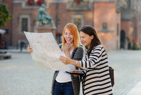 Two young female tourists on the streets of the old town. Girlfriends try to find their way in an unfamiliar city. They carefully consider the map of the area. Behind them are beautiful buildings and monument. Stock Photo