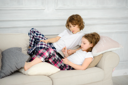 Two children, the boy and the girl, lie on a sofa with the tablet in hands. They with interest look at the screen. Hobby of modern children.