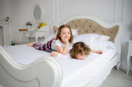 pranks: Brother and sister of primary school age play pranks on a bed. Them it is very cheerful. Stock Photo