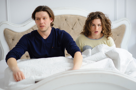 The young couple has overslept. The man and the woman sit in a bed. They have a sleepy and perplexed look. Stock Photo