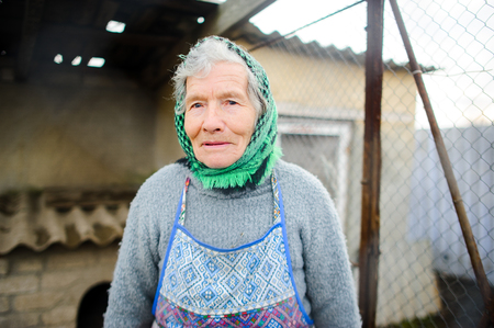 Old peasant woman. Calm, wise sight. gray hair from under a scarf. Wrinkled face. Stock Photo