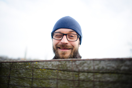 Funny young man with glasses and a beard looks out from behind the fence. He looks at the camera and winks gaily. Stock Photo