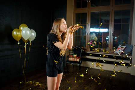 Beautiful young birthday girl after the end of a party. Girl blows off gold confetti from palms. She one in a make-up room. Flowers, balloons, gifts remind of a holiday. Stock Photo