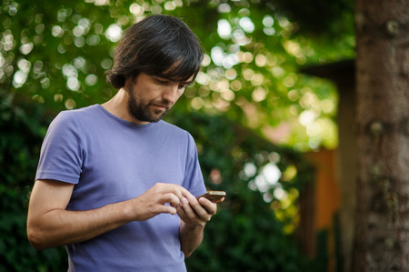 Young bearded guy looks thoughtfully at the screen of the smartphone. Summer. Park. Wide possibilities of modern communication. Stock Photo