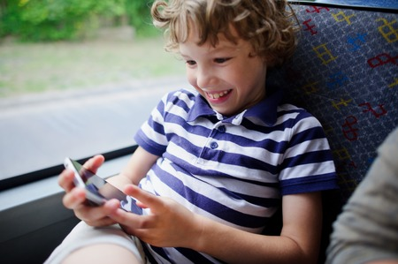 A small passenger of a city bus with a smartphone in hand. The boy looks at the smartphone screen and cheerfully smiles. Stock Photo