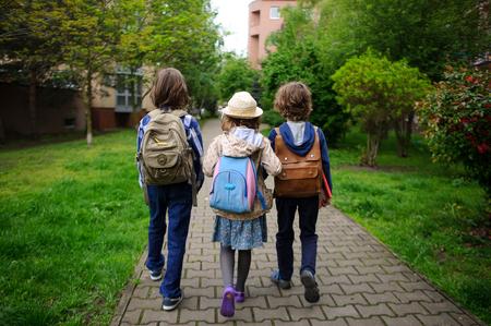 Kleine Schulstudenten beeilen sich auf Berufe. Hinter Schultern bei Kinderschultaschen. Warmer Morgen Helle Frühlingsgrüns des Parks.