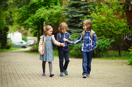 Three little friends go to school. Behind shoulders at children schoolbags. Warm spring morning. To little school students cheerfully together. Stock Photo