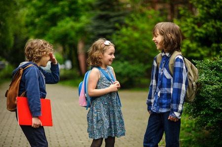 Pupils of elementary school about something cheerfully talk on the schoolyard. Children have a good mood. Warm spring morning. Stock Photo